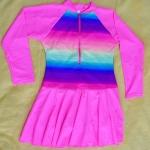 ชุดว่ายน้ำเด็กผู้หญิงสีชมพู ลายสีรุ้ง แขนยาว ข้างในเป็นกางเกงขาสั้น ด้านนอกเป็นกระโปรง มีซิบด้านหน้า
